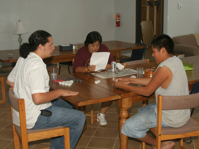 American Indian kids playing games around the table.