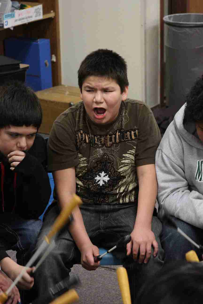 Lakota boy singing while playing the drum.