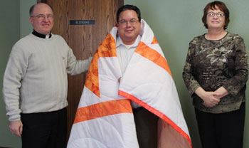 St. Joseph's Indian School presents a Lakota star quilt in appreciation for Fr. Jack's time on the board.