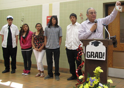 St. Joseph's 2013 Distinguished Alumnus, Del Iron Cloud, presents a gift to the Lakota graduates.