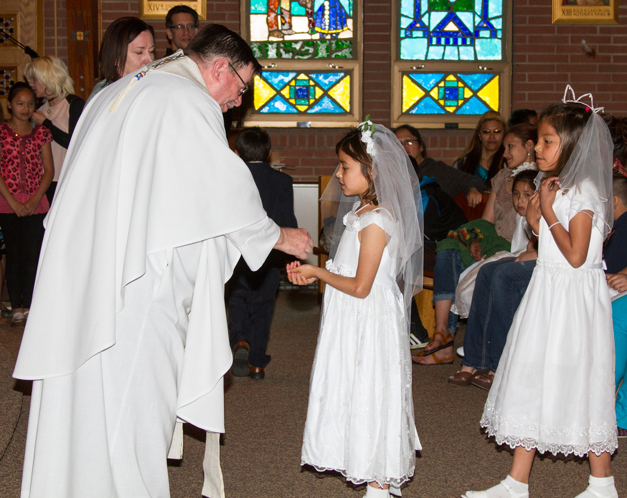 Fr. Anthony gives a Lakota child her First Holy Communion.