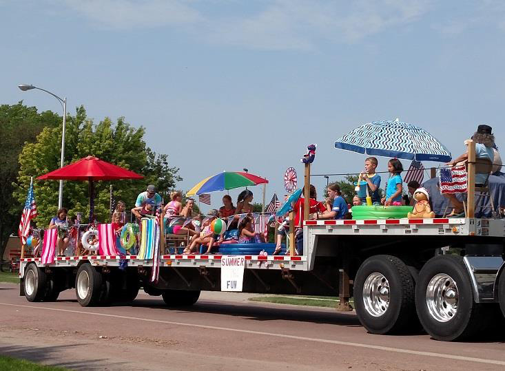 "One float in the parade had a ""Summer fun"" theme, complete with squirt guns to cool off the crowd."