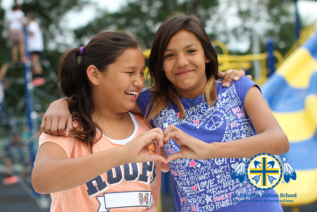 Two girls create a heart shape with their hands on the playground