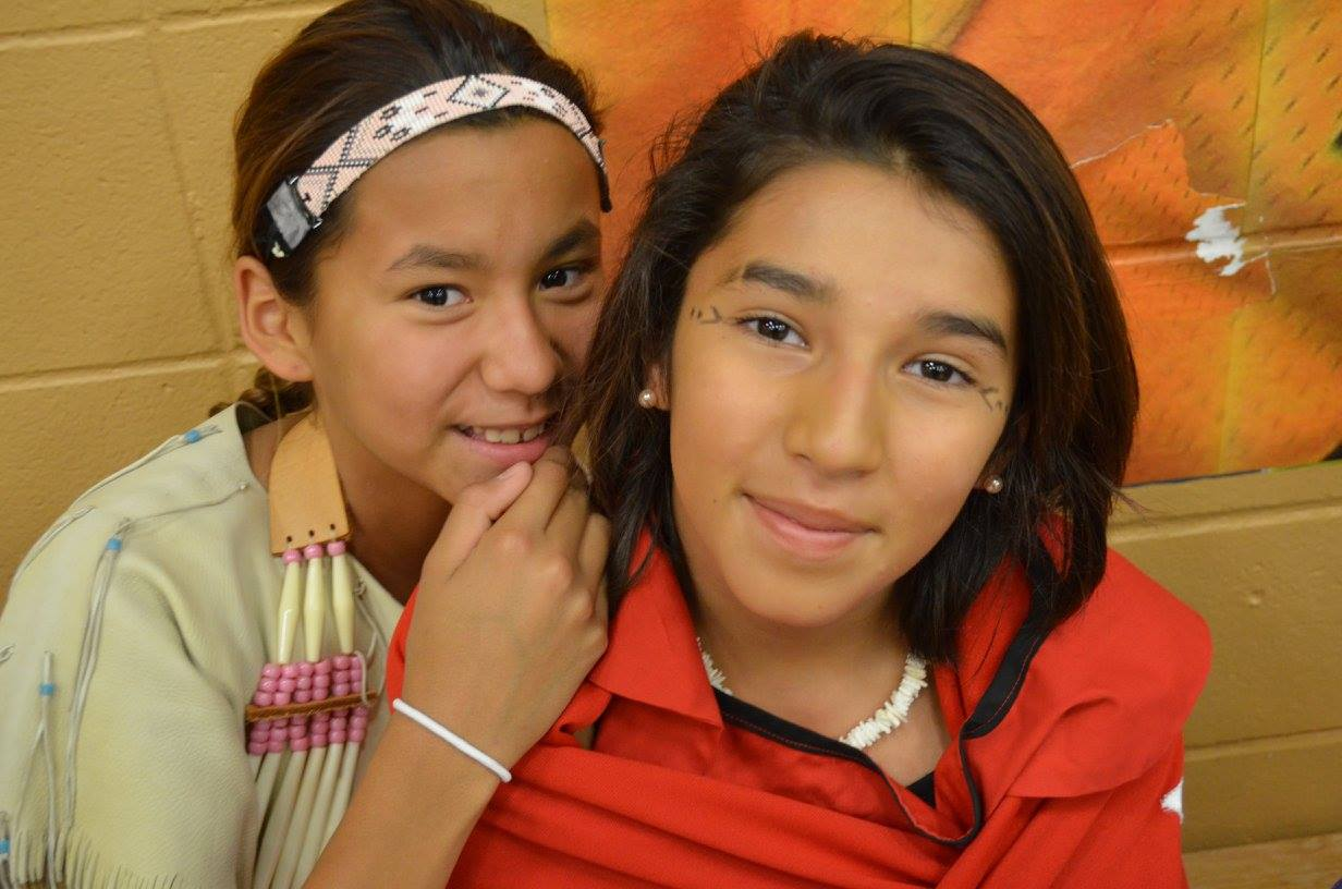 Two Lakota(Sioux) girls dressed in regalia await their turn.