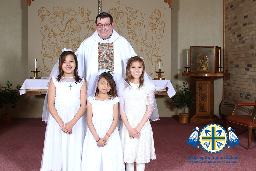Fr. Anthony with three Lakota (Sioux) students at Our Lady of the Sioux Chapel in Chamberlain, SD.