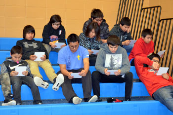 A group of St. Joseph's junior high boys are pictured sitting on the bleachers. Their eyes are glued to their bingo cards.