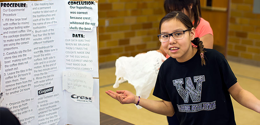 A fourth grade girl stands in front of her display board explaining her science project about tooth whitening.