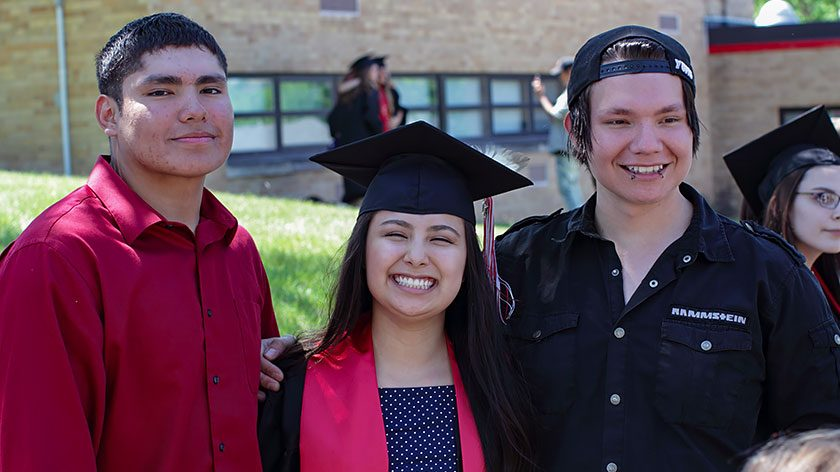 A young Native American graduate smiles broadly in her cap and gown with a friend on either side.